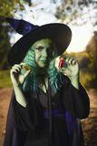 Young girl with green hair and skin suit of witch in forest holds small bottles with red and orange potion. Halloween time Stock Images