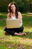 Young girl on a green meadow with a laptop Stock Photos