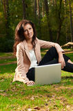 Young girl on a green meadow with a laptop Stock Photography