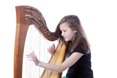 Young girl in green pants plays harp in studio Royalty Free Stock Photo
