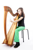 Young girl in green pants plays harp in studio Stock Photos