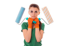 A young girl in the green shirt is worth having and holding the hands of two rollers for painting Royalty Free Stock Photo