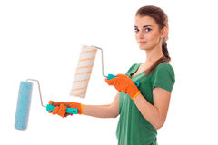 A young girl in the green shirt is worth turning sideways looks at the camera and holding rollers for painting Stock Image