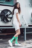 Young girl in green socks and white dress on the street. Streetstyle, fashion. Young girl in green socks and white dress on the street. Propellers on background Royalty Free Stock Image