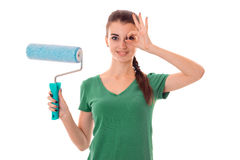 A young girl in a green t-shirt holding a roller to paint walls isolated on white background Royalty Free Stock Photography