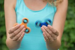 A young girl holding and twisting two spinners of blue and orang. A young girl in a green T-shirt is holding and twisting two spinners of blue and orange in the Royalty Free Stock Photography