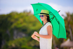 Young girl with green umbrella on white beach Royalty Free Stock Image