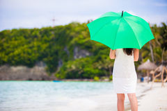 Young girl with green umbrella on white beach Stock Photo