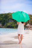 Young girl with green umbrella on white beach Royalty Free Stock Photography