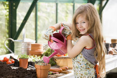 Young girl in greenhouse watering potted plant