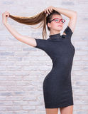 Young girl in grey dress pulls her long hair tail Stock Images