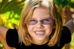 Young Girl Grinning. A young girl leans forward with a big smile and her hands on her hips.  She is blond and is wearing glasses.  Model released Stock Image