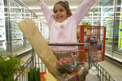 Young girl grocery shopping in frozen foods section royalty free stock photo