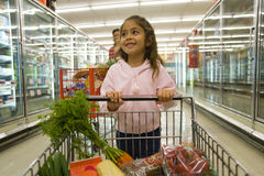 Young girl grocery shopping in frozen foods section Royalty Free Stock Images