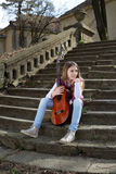 Young Girl With Guitar Sitting on the Stone Stairs and Looking Away Stock Image