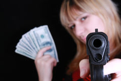 Young girl with gun and money Royalty Free Stock Photos