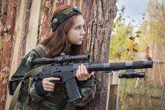 Young girl with a gun peeking from behind cover. Young girl with a gun playing laser tag Royalty Free Stock Photography
