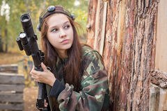 Young girl with a gun peeking from behind cover. Young girl with a gun playing laser tag Stock Image