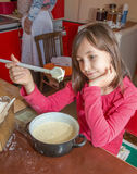 Young girl gustation at the cooking Stock Photography