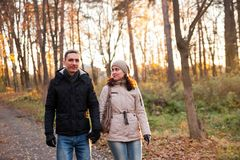 Young girl with guy in autumn park. Portrait of women and men on walk in autumn forest royalty free stock image