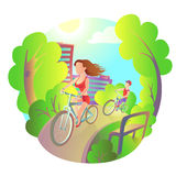 Young girl and guy on a bike ride around the city park. Activity outdoor sports. Cyclists travel. Young girl and guy on a bike ride around the city park Stock Photo