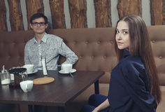 Young girl with a guy in a cafe sits on the couch half turned Royalty Free Stock Photo