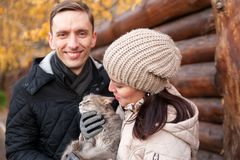 Couple on walk in autumn park with cat. Young girl and guy with cat in autumn park royalty free stock image