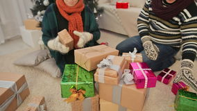 A young girl and a guy are gathering a bunch of New Year gifts. Christmas theme. Accelerated shooting. stock footage