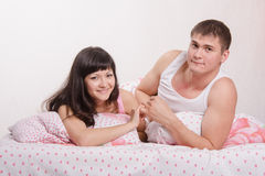 Young girl and the guy put up, lying in bed stock photos