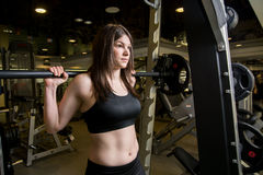 Young girl in the gym with a barbell. Royalty Free Stock Image