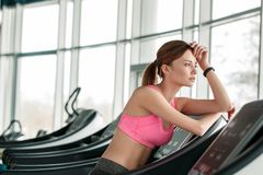 Young girl in gym healthy lifestyle leaning on treadmill looking out the window thoughtful stock photography