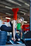 A young girl in the gym sits on pancakes for a bar. stock photography