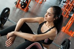 Young woman in gym sporty lifestyle sitting near barbell looking down exhausted cllose-up royalty free stock photo