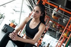 Young woman in gym sporty lifestyle sitting looking forward thoughtful stock photos