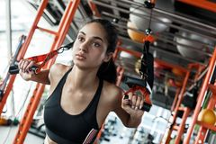 Young woman in gym sporty lifestyle total resistance workout pulling suspansion straps close-up motivated stock photos