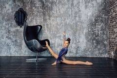 A young girl gymnast in a blue suit does stretching exercise near the chair against the gray wall and smiles stock images