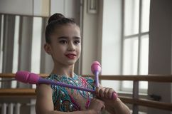 Young girl gymnast with clubs in hands in the gym. Young girl gymnast with clubs looks through a large window in the hall stock photography