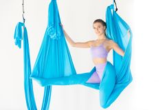 Young girl gymnast in sportswear doing stretching on blue hammock in white studio. Concept aero fly yoga.  royalty free stock photo