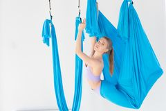 Young girl gymnast in sportswear doing stretching on blue hammock in white studio. Concept aero fly yoga.  stock images