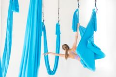 Young girl gymnast in sportswear doing stretching on blue hammock in white studio. Concept aero fly yoga.  stock photos