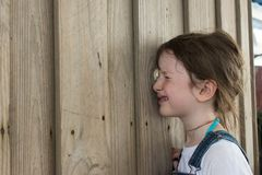 Young girl peering through hole in fence. Young girl with hair pinned up peering through hole in fence outdoors Stock Photography