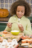 Young girl at Halloween making treats and smiling Stock Images
