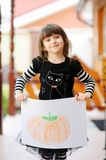 Young girl with Halloween pumpkin drawing. Young girl in black cat dress shows Halloween pumpkin drawing stock photography