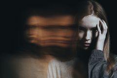 Young girl with hallucinations. Young girl addicted to drugs with hallucinations against blurred background royalty free stock photography