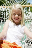 Young girl on hammock. A smiling young blond girl sitting in a hammock on a sunny summer day Stock Images