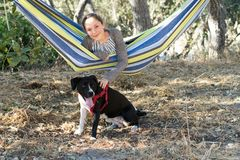 Young Girl in a Hammock Playing with Dog Stock Photos