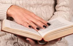 Young Girl hand with black nails holds book, woman in sweater reading book. Young Girl hand with black nails manicure holds book, woman in wool sweater reading stock photo