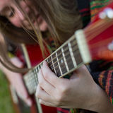 Young girl hand playing on acoustic guitar. Stock Image