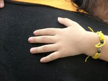Young girl hand wearing King symbol wrist band on her father shoulder. People gather to attend symbolic Royal bathing of King Bhumibhol of Thailand. The King stock images
