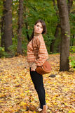 Young girl with handbag standing in the forest Stock Photos